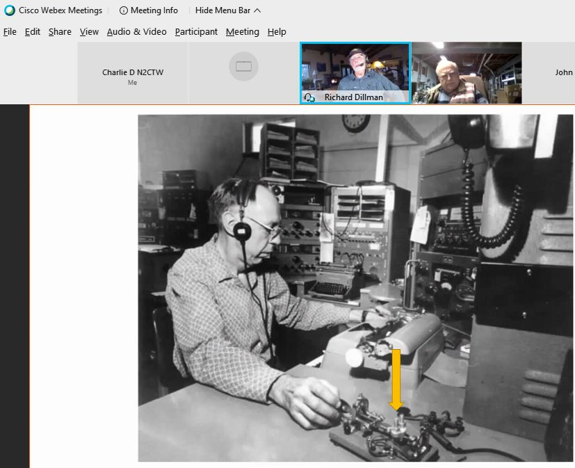photo shows operator seated at a radio operator station, sending morse code